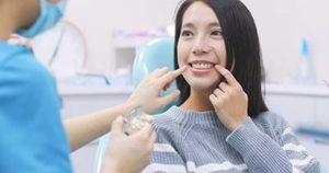 woman at the dentist pointing out her cracked tooth during cosmetic dentistry in Upper Kirby TX