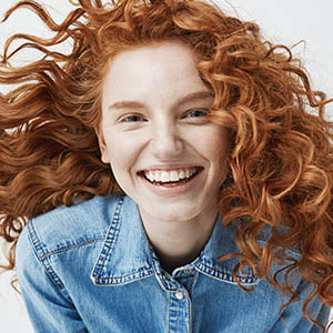 red haired girl smiling from years of general dentistry teeth cleaning and dental exams in tx