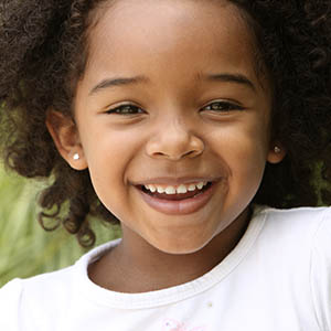 african american girl smiling in the park after going to pediatric dentistry in upper kirby tx