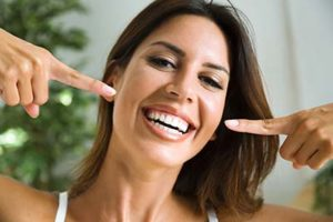 woman pointing out her beautiful smile from teeth whitening services in Upper Kirby, Texas