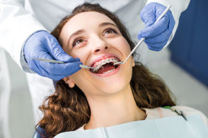 teenage girl having dental braces in tx adjusted during orthodontic services in tx