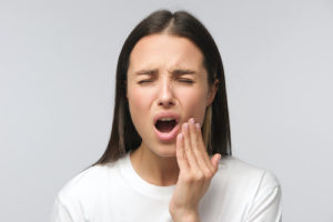 woman struggles with the pain caused by impacted teeth